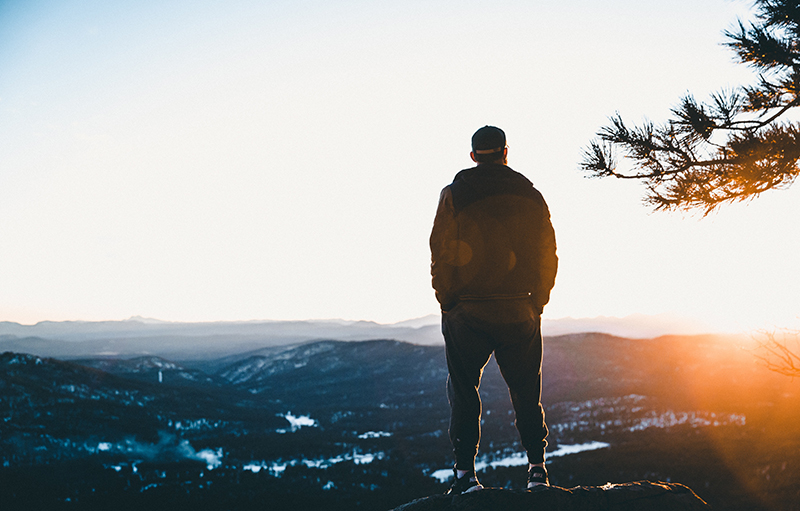 Man standing on top of a mountain, looking at the sun