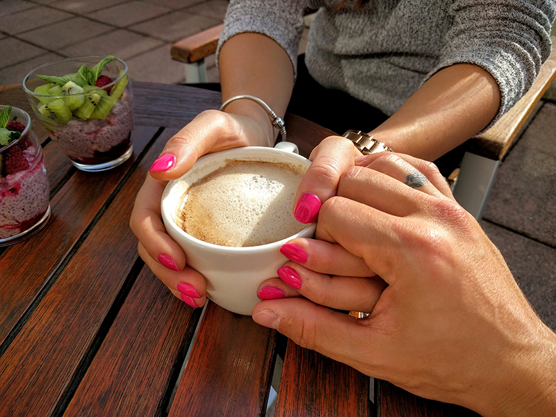 Two people holding hands and a cup of coffee